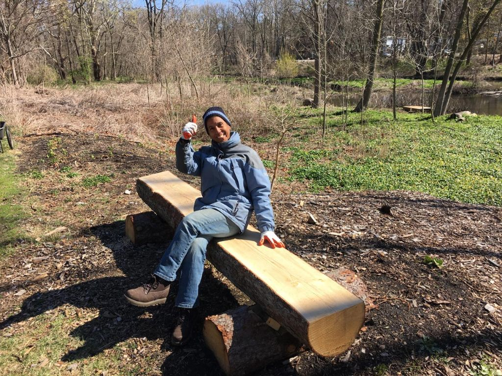 man sitting on a wood bench giving the thumbs up